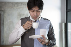 Asian younger man drinking hot beverage in white cup Royalty Free Stock Photos