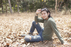 Asian younger man sitting on dry leaves field with smiling face Royalty Free Stock Photos