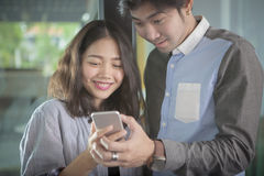 Asian younger man and woman looking to smart phone screen toothy Royalty Free Stock Image