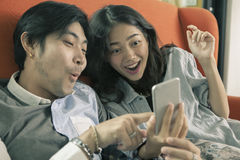 Asian younger man and woman watching on smart phone with surpris Stock Photos