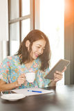 Asian younger woman reading message on computer tablet toothy sm Stock Photos