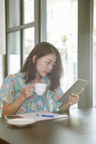 Asian younger woman reading news from social media and other han. D holding hot coffee cup in home living room Royalty Free Stock Photo