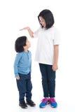 Asiangirl mäter tillväxten av hennes broder Arkivfoto