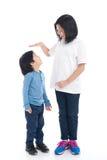 Asiangirl mäter tillväxten av hennes broder Arkivbilder