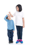 Asiangirl measures the growth of her brother. On white background isolated Royalty Free Stock Image