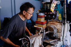 Asians Craftsman being machined steel in a factory Stock Images