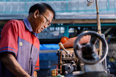 Asians Craftsman being machined steel in a factory Stock Photography