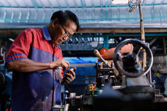 Asians Craftsman being machined steel in a factory Royalty Free Stock Images
