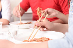 Asians eating with sticks Royalty Free Stock Photo