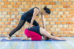 Asians female trainer helping young woman doing yoga Stock Image