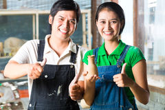 Asians with handmade pottery. Two Asians or Indonesians holding proud baked clay and a finished handmade vase stock images