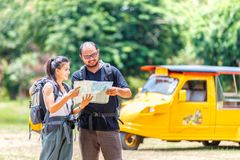 Asians love couple enjoying look at map travel with yellow taxi or tuk tuk touring background, Ayutthaya Province. Thailand royalty free stock photo