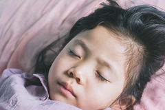 Close up Cute a little Asian girl are sleeping. Asians love to sleep on the bed with the tired of playing and healthy children from the rest Royalty Free Stock Photo