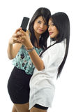 Asians photographing themselves. Two asian women taking a picture of themselves with a mobile phone, isolated on white royalty free stock images