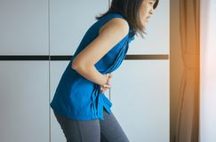 Asians woman having painful stomachache and gastritis,Female suffering from abdominal pain,Hand squeezing belly. Asians woman having painful stomachache and stock photo
