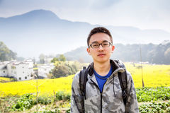 Asians. Young chinese man posing in front of spectacular countryside stock image