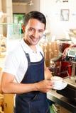 Asiat Coffeeshop - baristaen framlägger kaffe Arkivfoto