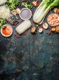 Asiat, der Bestandteile kocht: Reisnudeln, pok choy, Soßen, Garnelen, Paprika und Shiitakepilze auf dunklem Hintergrund, Draufsic Lizenzfreie Stockfotografie