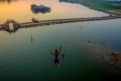 Asiat Guy Jump från den måndag bron arkivfoton