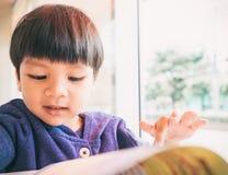 Asiatet 4 år gammal pojke läser en rolig bok Arkivbilder