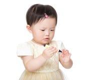Asiatet behandla som ett barn den hållande färgpennan för flickan arkivbild