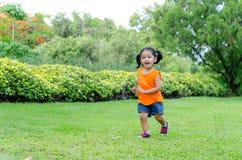Asiatet behandla som ett barn flickaleende och spring Arkivfoto