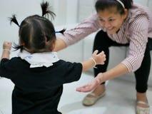 Asiatet behandla som ett barn flickan som går in mot hennes moder, medan modern som framåtriktat lutar med händer som ut når klar Royaltyfria Bilder