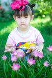 Asiatet behandla som ett barn flickan med blomman Royaltyfri Foto