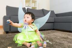 Asiatet behandla som ett barn flickan med den halloween partidressingen och spelar leksakkvarteret Royaltyfria Bilder