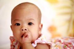 Asiatet behandla som ett barn flickan som suger hennes tumme Royaltyfri Bild