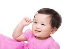 Asiatet behandla som ett barn flickan trycker på hennes öra Arkivbild