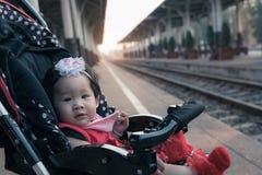 Asiatet behandla som ett barn flickasammanträde i sittvagn i järnvägsstation Arkivbilder