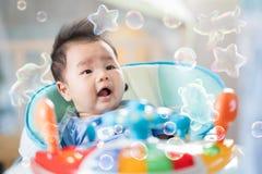 Asiatet behandla som ett barn leende på leksakbilen Royaltyfri Foto