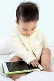 Asiatet behandla som ett barn lekleken med minnestavlaPC Royaltyfria Bilder