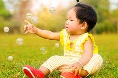 Asiatet behandla som ett barn lyckligt i gräs i moring tid med solljus Arkivfoto