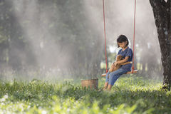 Asiatet behandla som ett barn på gunga med valpen Arkivbild