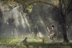 Asiatet behandla som ett barn på gunga med valpen Arkivfoto