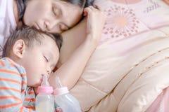Asiatet behandla som ett barn pojken som sover i moderarm Arkivfoton