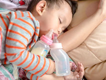 Asiatet behandla som ett barn pojken som sover i moderarm Royaltyfri Foto
