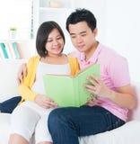 Asiatet kopplar ihop läsning bokar tillsammans arkivfoton