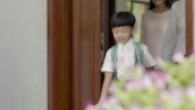 Asiatet uppfostrar öppningsdörren för att son ska gå ut för att gå till skolan