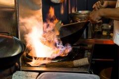 Asiatet wokar matlagning med flammor i en öppen kitc för stilgatamat arkivbild
