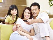 Asiatföräldrar och hållande ögonen på TV för dotter hemma royaltyfria bilder