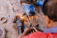 Asiathantverkare som använder gassvetsningstål i en fabrik royaltyfri fotografi