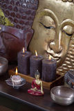 Asiatic decoration in brown and gold with buddha and candles. Royalty Free Stock Image
