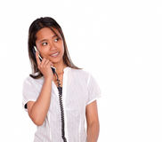 Asiatic young woman looking left speaking on phone Royalty Free Stock Images
