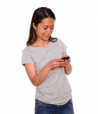 Asiatic young woman sending a message Royalty Free Stock Images