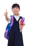 Asiatico cinese poca ragazza della scuola primaria che mostra i pollici su Immagine Stock Libera da Diritti