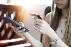 Asiatico della donna che per mezzo del telefono e carta di credito che compera fuoco online e selettivo a disposizione fotografia stock libera da diritti