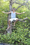 Asiatico Guy Sitting On The Tree immagini stock libere da diritti